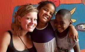 una giovane volontaria con due bambini di colore