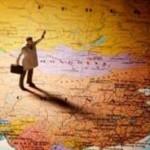 statuina con valigia sopra una cartina geografica